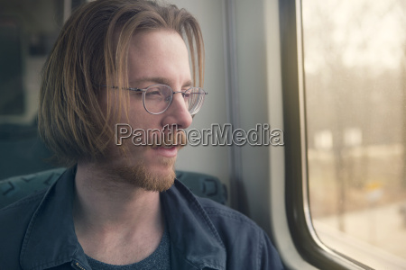 red haired man sitting in train
