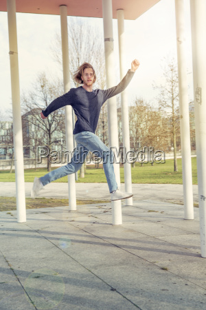 young man with red hair jumping