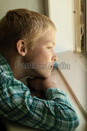 kind mit traurigem ausdruck sitzt in
