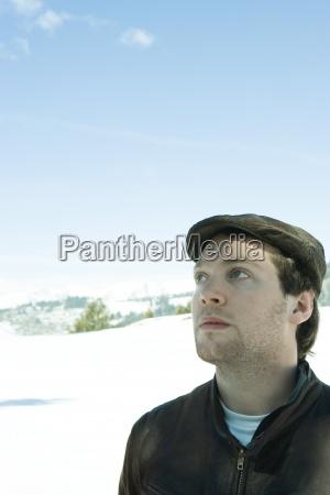 junger mannden hut in der verschneiten