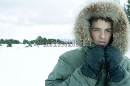 teen jungen tragen parka in verschneite