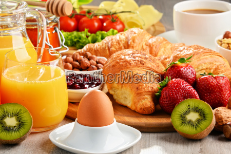 breakfast consisting of croissants coffee fruits