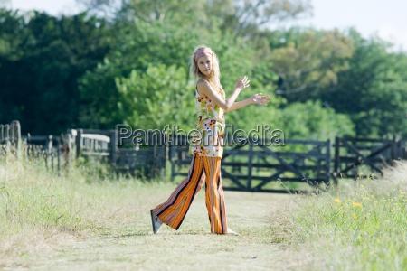 young woman walking in rural field