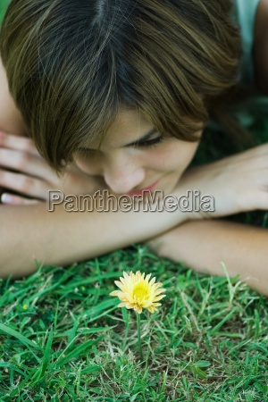young woman lying on grass looking