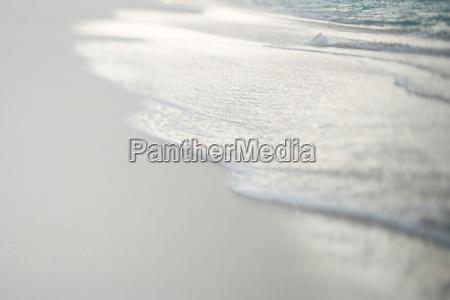 surf washing up on sand close