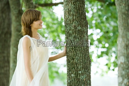young woman standing in woods touching