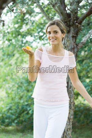 woman holding slice of orange out