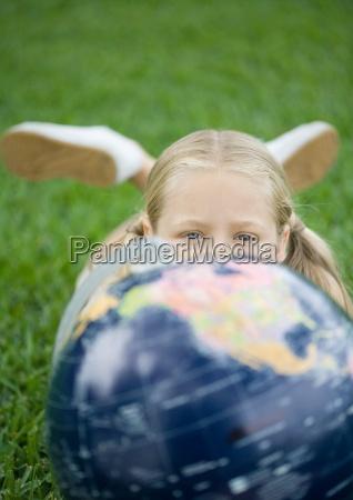 maedchen das auf gras mit globus