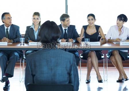 geschaeftsleute in ausschusssitzung im vordergrund mit