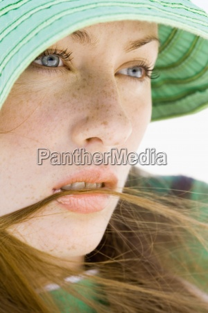 young woman wearing sun hat close