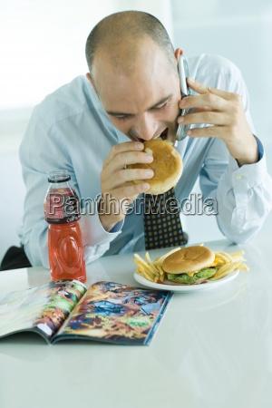 mann isst hamburger handy und blick