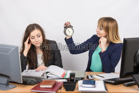 zwei junge huebsche geschaeftsfrau sitzt an