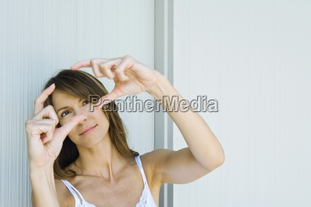 woman holding up finger frame looking