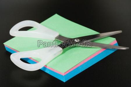 scissors resting on blank paper close