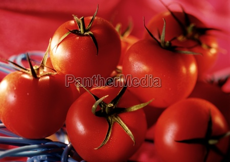 pile of red tomatoes with green