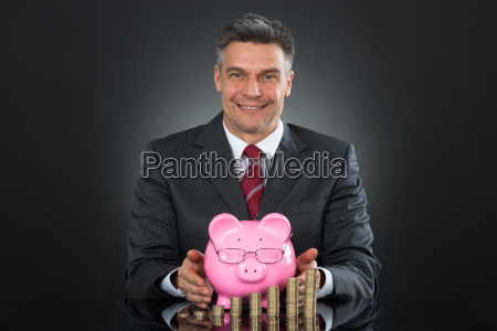 businessman sheltering coins and piggybank at