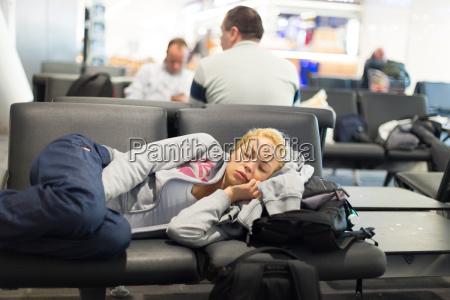 muede weibliche reisende schlafen auf flughafen
