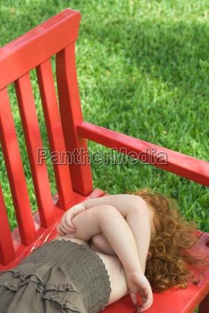little girl lying on red bench