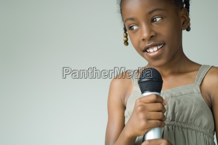 girl holding up microphone looking away