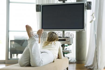 female lying on stomach watching flat