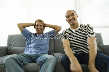 two men sitting on sofa laughing