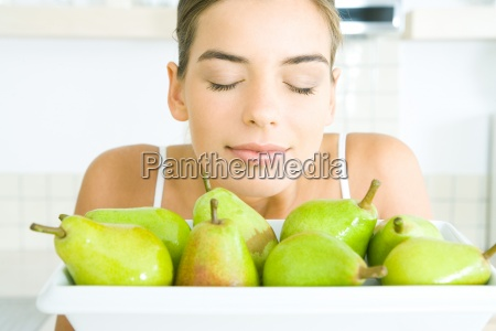 young woman smelling fresh pears eyes