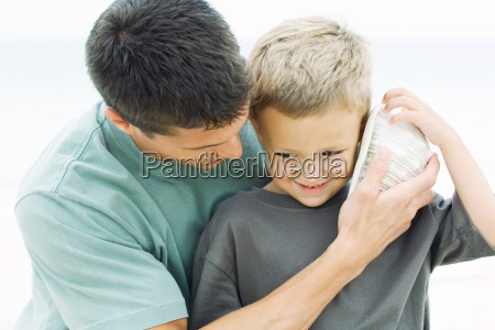 father holding seashell up to young