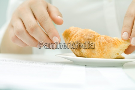 woman picking up croissant close up