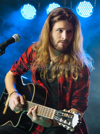 man playing acoustic guitar in concert