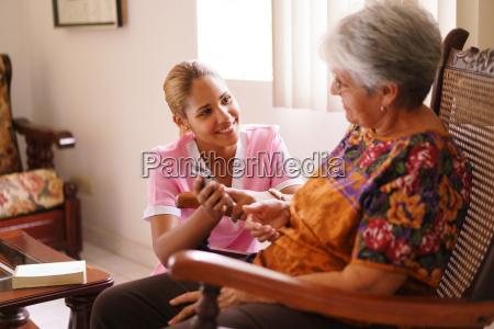 hospiz krankenschwester hilft alte dame mit