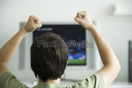 male watching television fists raised in