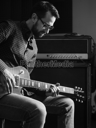 concentrating on his electric guitar playing