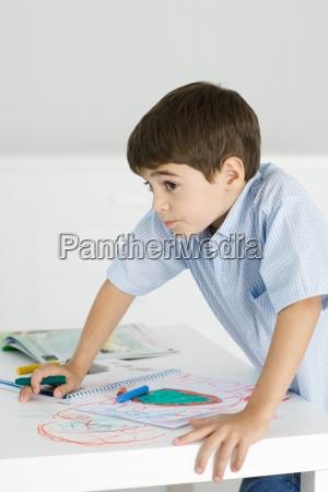 boy stuetzte sich auf tisch haelt