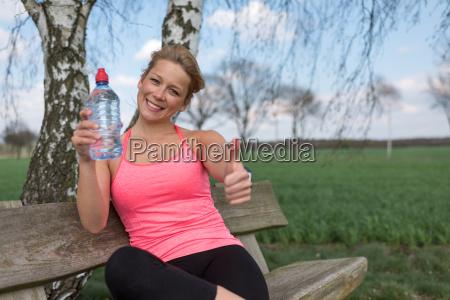 joggerin sitzt draussen auf der bank