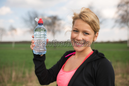 blonde joggerin auf einer wiese mit