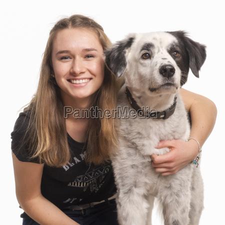 smiling girl hugs her dog