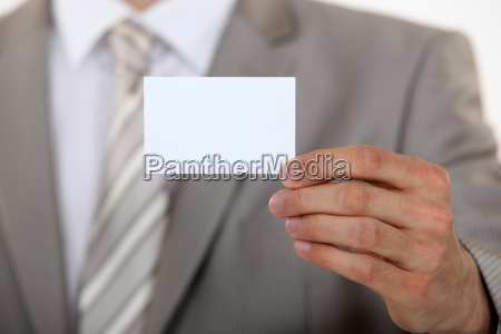 man holding up business card