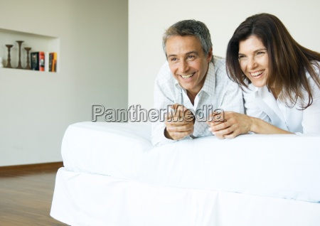 mature couple lying on bed watching