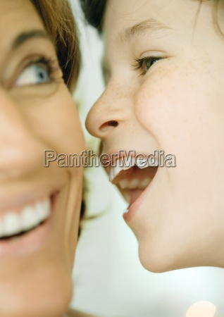 boy whispering to woman close up