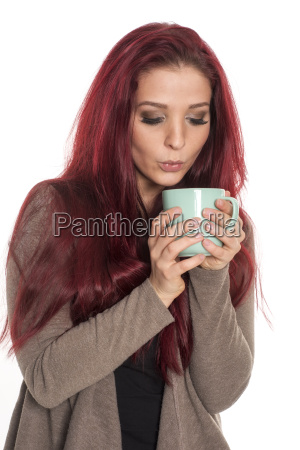 young red haired woman blows into