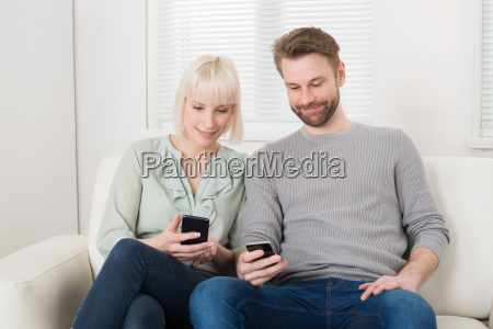 couple sitting on couch using cellphone