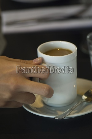 womans hand picking up cup of