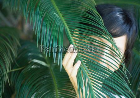 woman standing amongst palm leaves head