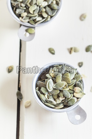 two cups of pumpkin seeds on