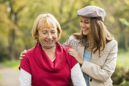 smiling senior woman and granddaughter walking