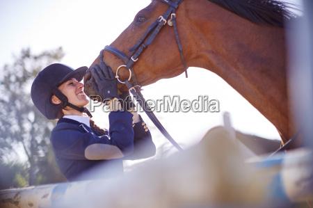 laechelnde junge frau mit pferd auf