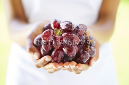 womans hands holding red grapes