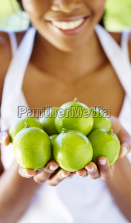 womans hands holding limes