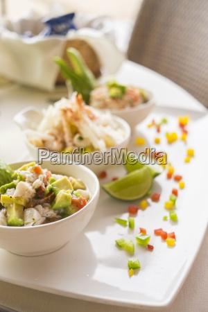 three bowls of marinated raw seafood