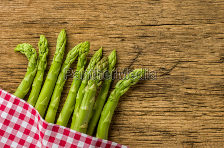 green asparagus on rustic wood background